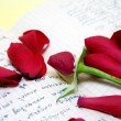 Rose petals on the old script — Stock Photo