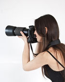 A young female photographer with a professional camera — Stock Photo