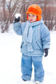 Little boy playing snowballs; snowman sculpts; digs snow; — Stock Photo