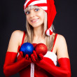 Stock Photo: Santa girl holding a Christmas ball, Christmas toys.Holidays Christmas And