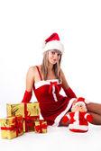 Santa moça está sentada em suas mãos em uma pilha de presentes. férias de natal — Foto Stock