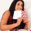 Stock Photo: Girl lying in bed with gifts, cards, hearts