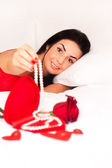 In love with girl lying in bed, strewn with hearts and roses — Stock Photo