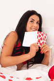 Girl lying in bed with gifts, cards, hearts — Stock Photo