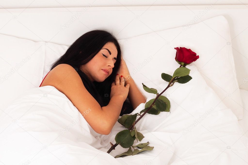 A beautiful young girl lying in bed with gifts, roses, woke up, asleep. — Stock Photo #4736686