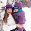 Winter's day a happy family, mom and baby, snow, park, walk — Stock Photo