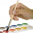 Foto Stock: Watercolors and hand with paintbrush