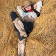 Stock Photo: Cowboy girl lying in a field of grass