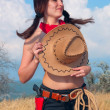 Girl cowboy in the field with  hat on  chest — Stock Photo