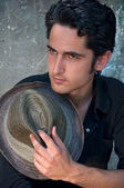 Young man sitting and holding a hat — Stock Photo
