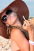Attractive woman in a hat smoking a cigarette — Stock Photo