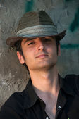 Young man sitting in hat near wall — Stock Photo