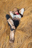 Cowboy girl lying in a field of grass — Stock Photo