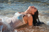 Beautiful girl in the sea in the waves — Stock Photo