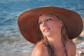 Beautiful girl in the hat on the beach — Stock Photo