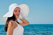 Beautiful girl on the beach in the hat — Stock Photo