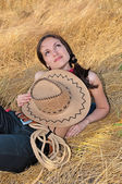 Beautiful woman lying in the straw with the hat — Stock Photo