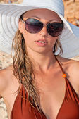 Beautiful woman in a hat and sunglasses in a bikini — Stock Photo