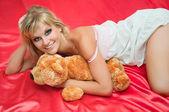 Pembe üzerinde bir yatakta çekici genç kadın — Stok fotoğraf