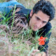 Young man on the grass with a flower — Stock Photo