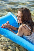 Beautiful woman on a mattress on the sea — Stock Photo