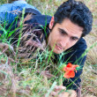Young man  on the grass with flower — Stock Photo