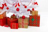 Presents under white christmas tree — Stock Photo