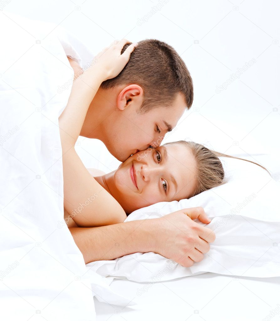 Young couple in bed, man kissing the happy woman — Stock Photo #4511143