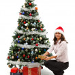 Young woman near christmas tree with presents — Stock Photo