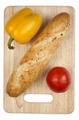 Uncutted bread with vegetables — Stock Photo