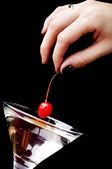 The hand putting the red cherry to the martini glass — Stock Photo