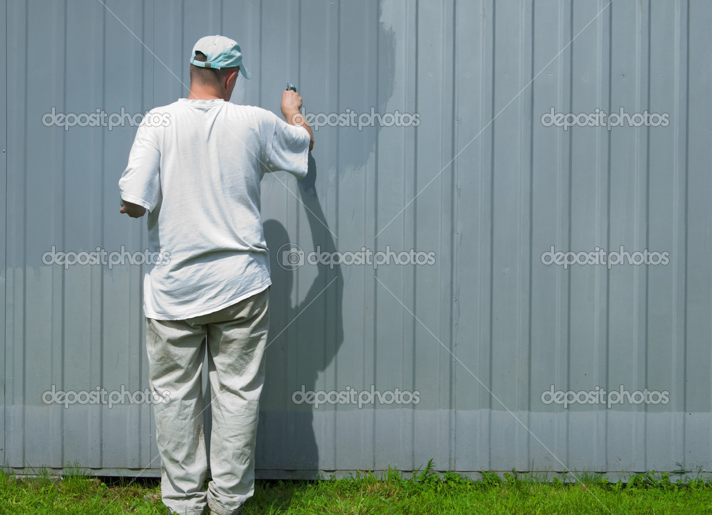 A worker dyes a metallic fence — Stock Photo #4464298