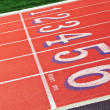 Lanes of a red race track with numbers and green football field — Stock Photo
