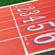 Lanes of a red race track with numbers and green football field - Foto de Stock