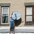 Male on a ladder installing a tv dish - Stock Photo