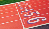 Lanes of a red race track with numbers and green football field — Photo