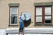 Male on a ladder installing a tv dish — Stock Photo
