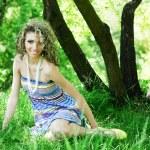 Beautiful young woman sitting on grass — Stock Photo