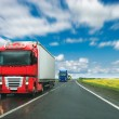 Trucks at country road at sunny day - Stock Photo