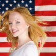 Beautiful teen girl against american flag — Стоковая фотография