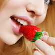 Girl eating strawberry — Stock Photo