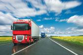 Trucks at country road at sunny day — Stock Photo