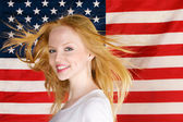 Beautiful teen girl against american flag — Photo