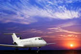 Jet airliner on ground and stunning sunset — Stock Photo