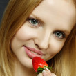 Young woman tasting strawberry — Stock Photo