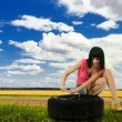 Stock Photo: Young womrepair car wheel