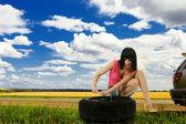 Young woman repair car wheel — Stock Photo