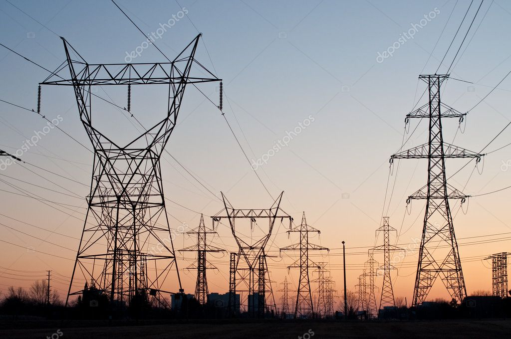 A long line of electrical transmission towers carrying high voltage lines.  Stock Photo #3936429