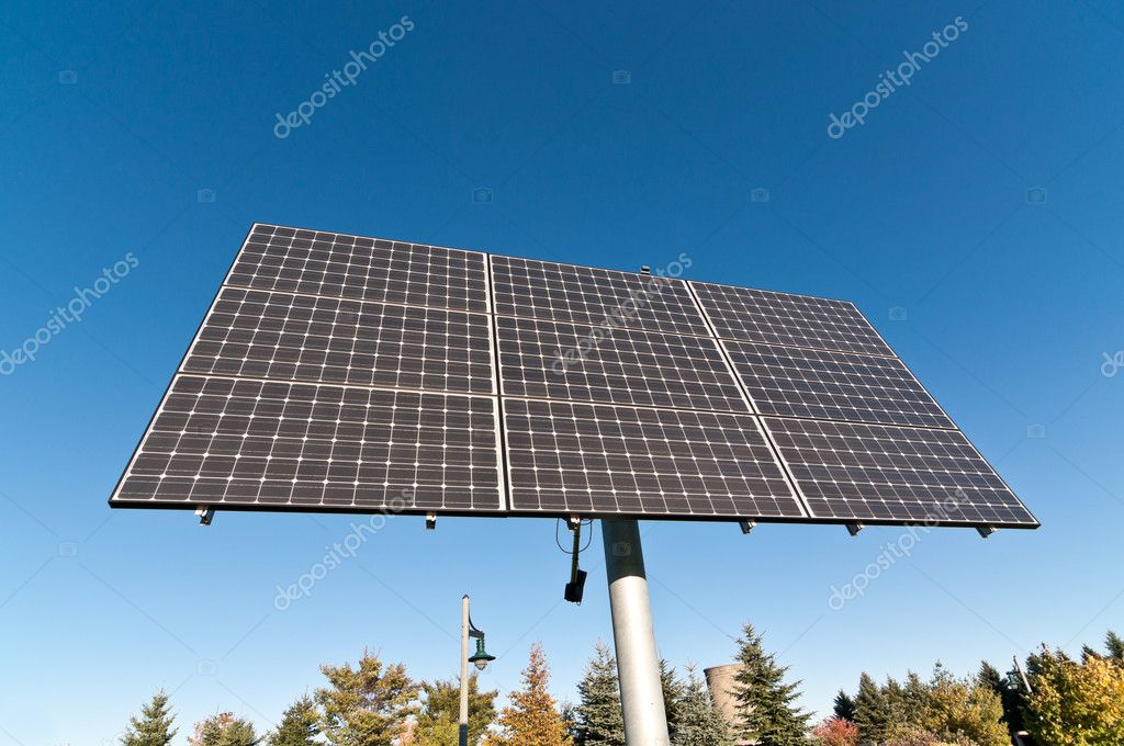 A photovoltaic solar panel array in a park with a blue sky in the background. — Stock Photo #4019255