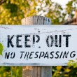 Weathered Keep Out Sign on a Wooden Post — Stock Photo